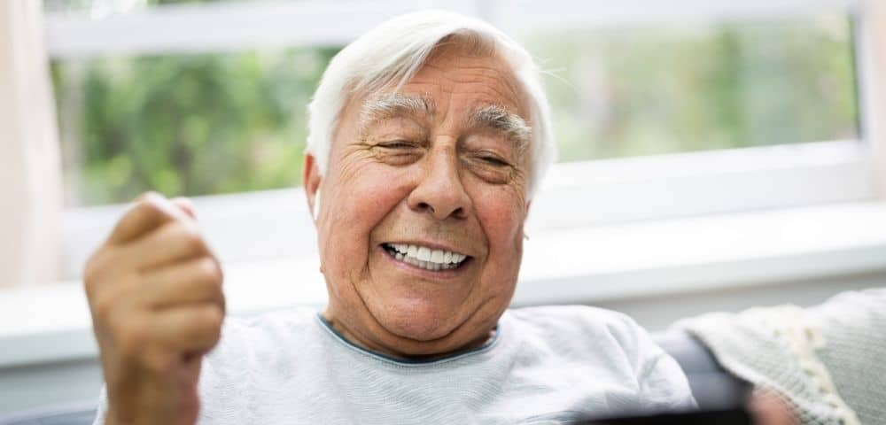 senior aged man smiling and showing off new teeth