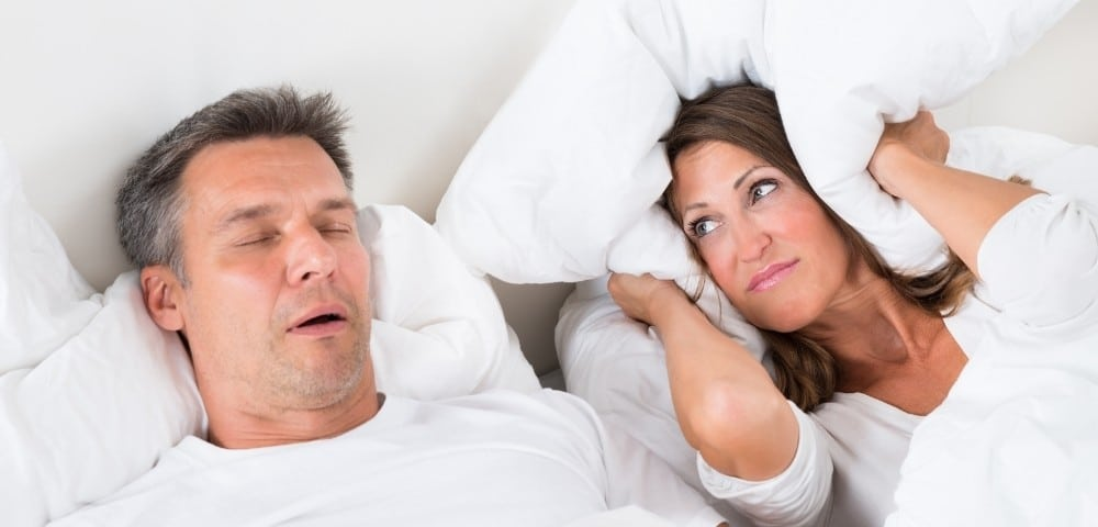 Woman struggling to sleep due to her partner's sleep apnea issues.